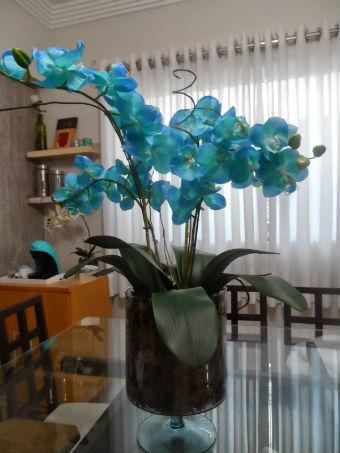 Um vaso de orquídeas azuis sobre uma mesa na sala